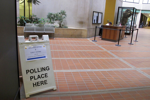 A sign directs voters to an early voting location in a state office building on Tuesday, Aug. 11, 2020, in Juneau, Alaska. Voting in Alaska will look a bit different amid the coronavirus pandemic, with election officials saying poll workers will be required to wear protective gear, such as masks, and will encourage voters to maintain social distance and wear masks. (AP Photo/Becky Bohrer)