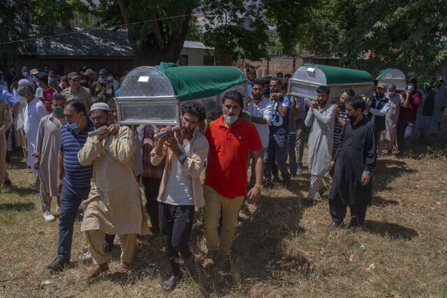 Relatives and party workers carry the coffins of a politician Sheikh Wasim Bari, his father and brother during their joint funeral in Bandipora town, north of Srinagar, Indian controlled Kashmir, Thursday, July 9, 2020. Unidentified assailants late Wednesday fatally shot Bari, a leader with Prime Minister Narendra Modi's Bharatiya Janata Party, along with his father and brother in Kashmir, police said, in a first major attack against India's ruling party members in the disputed region. (AP Photo/ Dar Yasin)