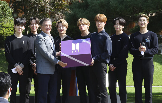 South Korean President Moon Jae-in, third from left, receives a gift from members of South Korean K-Pop group BTS during a ceremony marking the National Youth Day at the presidential Blue House in Seoul, South Korea, Saturday, Sept. 19, 2020. (Lee Jin-wook/Yonhap via AP)