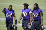 FILE - Baltimore Ravens guard John Urschel, left, speaks with teammates Robert Myers (70) and Leon Brown as they walk off the field after NFL football training camp in Owings Mills, Md., in this Wednesday, Aug. 5, 2015,  file photo. John Urschel has found that a master's degree in mathematics, his stature as an accomplished author and his pending PhD at MIT isn't necessarily enough to sell young students on the benefit of crunching numbers. What really makes him interesting to most kids is that he's a former NFL player who opted to immerse himself in math. (AP Photo/Patrick Semansky, File)