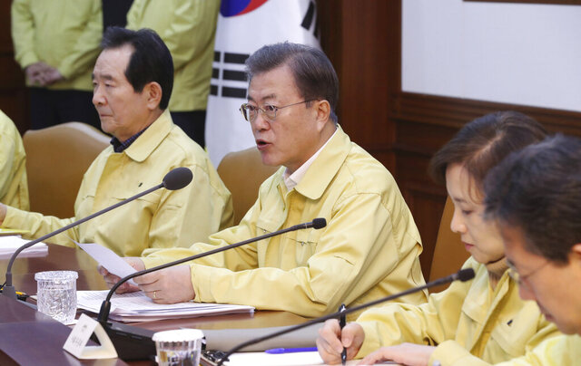 South Korean President Moon Jae-in, center, speaks during a meeting at a government complex in downtown Seoul, South Korea, Sunday, Feb. 23, 2020. South Korea's president has put the country on its highest alert for infectious diseases and says officials should take