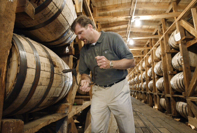 FILE – In this May 20, 2009, file photo, Jeff Arnett, the master distiller at the Jack Daniel Distillery in Lynchburg, Tenn., drills a hole in a barrel of whiskey in one of the aging houses at the distillery. After 12 years of leading production of the powerhouse Jack Daniel's whiskey brand, Arnett is stepping down as master distiller at the Tennessee distillery, the company announced Thursday, Sept. 3, 2020. (AP Photo/Mark Humphrey, File)