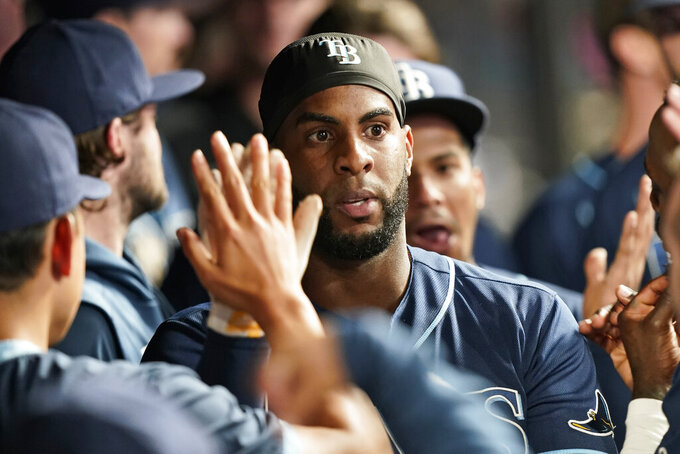 Tampa Bay Rays' Yandy Diaz celebrates with teammates after hitting a solo home run in the ninth inning of a baseball game against the Cleveland Indians, Thursday, July 22, 2021, in Cleveland. (AP Photo/Tony Dejak)