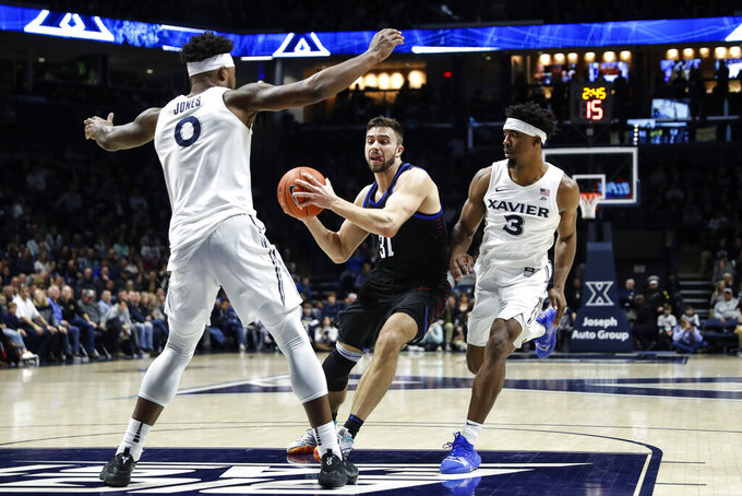 DePaul's Max Strus (31) drives against Xavier's Quentin Goodin (3) and Tyrique Jones (0) during the second half of an NCAA college basketball game, Saturday, Feb. 9, 2019, in Cincinnati. (AP Photo/John Minchillo)