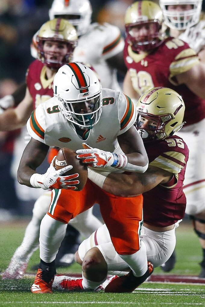 Boston College linebacker Isaiah McDuffie (55) tackles Miami tight end Brevin Jordan (9) during the first half of an NCAA college football game in Boston, Friday, Oct. 26, 2018. (AP Photo/Michael Dwyer)