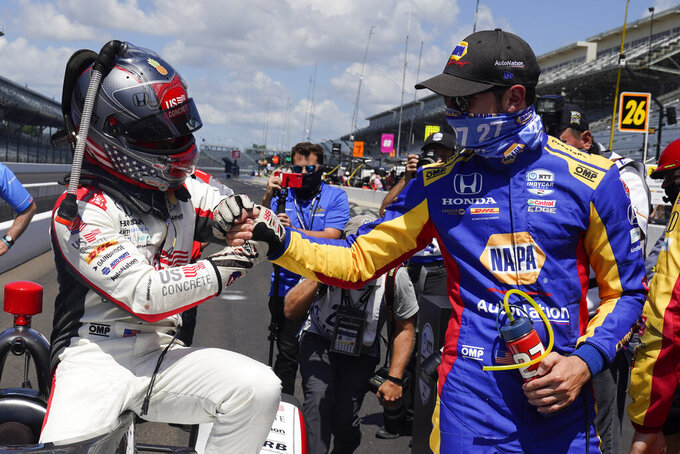 Marco Andretti is congratulated by Alexander Rossi after Andretti won the pole for the Indianapolis 500 auto race at Indianapolis Motor Speedway, Sunday, Aug. 16, 2020, in Indianapolis. (AP Photo/Darron Cummings)