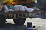 An Indian farmer sleeps at the back of his trawler during a blockade at the Delhi-Haryana state border, India, Sunday, Nov. 29, 2020. Protesting farmers on Sunday rejected the Indian government's offer to hold immediate talks if they ended their blockade of key highways they've held as they seek the scrapping of legislation they say could devastate crop prices.(AP Photo/Manish Swarup)