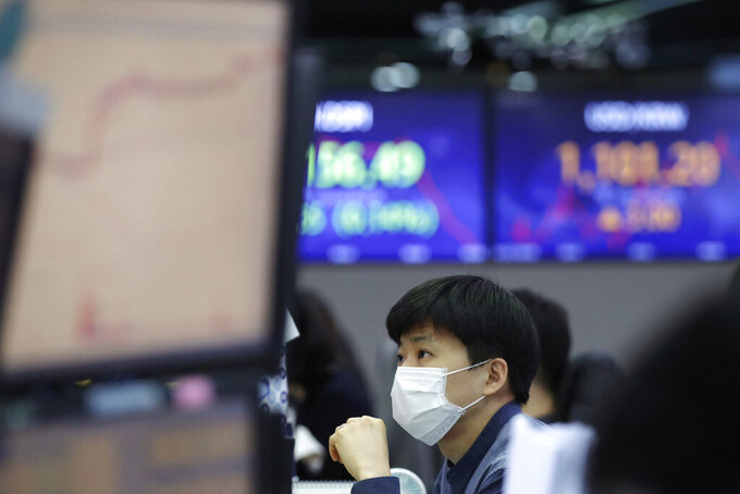 A currency trader watches computer monitors at the foreign exchange dealing room in Seoul, South Korea, Friday, Jan. 22, 2021. Asian stock markets retreated Friday after a resurgence of coronavirus infections in China and a rise in cases in Southeast Asia.(AP Photo/Lee Jin-man)