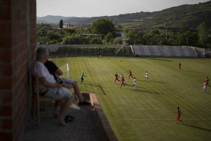 Residents watch a soccer match being played behind closed doors between Bylis Ballsh and Partizani Tirane from their rooftop in Ballsh, Albania, Monday July 6, 2020. The Albanian league game was played without fans to stop the spread of the coronavirus. (AP Photo/Daniel Cole)