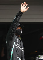 Mercedes driver Lewis Hamilton of Britain waves after clocking the fastest time during qualification for the Formula One Portuguese Grand Prix at the Algarve International Circuit in Portimao, Portugal, Saturday, Oct. 24, 2020. Hamilton will take pole position for the Formula One Portuguese Grand Prix which takes place on Sunday. (Jose Sena Goulao, Pool via AP)
