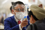 An employee wearing a protective mask and a face shield to help curb the spread of the new coronavirus measures the temperature of customers walking in food section of the Matsuya Ginza department store which partially reopens Monday, May 25, 2020, in Tokyo. Japan's Prime Minister Shinzo Abe is expected to remove a coronavirus state of emergency from Tokyo and four other remaining prefectures later in the day. (AP Photo/Eugene Hoshiko)