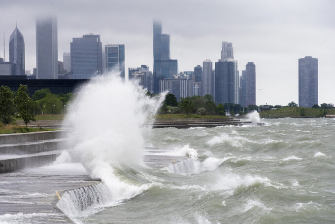 Waves up to 11 feet high crash into the lakefront trail near 31st Street Beach on the South Side of Chicago, Friday afternoon, May 28, 2021. The high waves closed most beaches to swimming Friday, the first day they were to be reopened since closing over a year ago because of the coronavirus pandemic. (Ashlee Rezin Garcia/Chicago Sun-Times via AP)