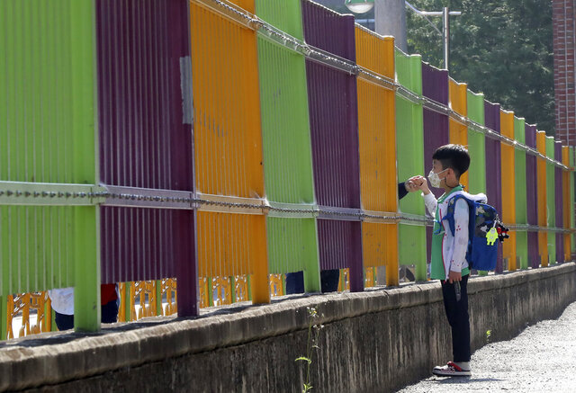 A pupil wearing a face mask to help protect against the spread of the new coronavirus holds his mother's hand through a fence as he arrives at the Ochi Elementary School in Gwangju, South Korea, Friday, May 29, 2020. (Park Chul-hong/Yonhap via AP)