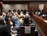 A heavy police presence stands in Superior Court of Cherokee County in Canton, Ga., on Tuesday, July 27, 2021, during Robert Aaron Long's plea hearing. Long, accused of killing eight people, most of them women of Asian descent, at Atlanta-area massage businesses pleaded guilty to four of the murders. He was handed four sentences of life without parole. (Ben Gray/Atlanta Journal-Constitution via AP, Pool)