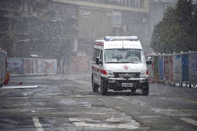 In this photo released by China's Xinhua News Agency, an ambulance drives along a road during a snowfall in Xiaogan in central China's Hubei Province, Saturday, Feb. 15, 2020.  The virus is thought to have infected more than 67,000 people globally and has killed at least 1,526 people, the vast majority in China, as the Chinese government announced new anti-disease measures while businesses reopen following sweeping controls that have idled much of the economy. (Hu Huhu/Xinhua via AP)
