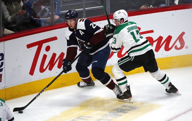 Colorado Avalanche center Nathan MacKinnon, left, looks to pass the puck as Dallas Stars center Mattias Janmark defends in the first period of an NHL hockey game Tuesday, Jan. 14, 2020, in Denver. (AP Photo/David Zalubowski)