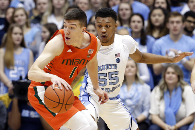 Miami guard Dejan Vasiljevic (1) dribbles while North Carolina guard Christian Keeling (55) defends during the first half of an NCAA college basketball game in Chapel Hill, N.C., Saturday, Jan. 25, 2020. (AP Photo/Gerry Broome)