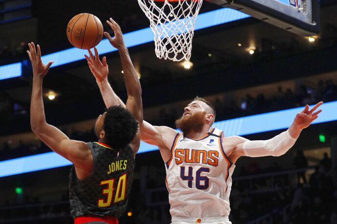 Phoenix Suns center Aron Baynes (46) battles Atlanta Hawks center Damian Jones (30) for a rebound in the first half of an NBA basketball game Tuesday, Jan. 14, 2020, in Atlanta. (AP Photo/John Bazemore)
