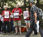 Jim Hill of Denver, Colo., from left, joins Shawn Summers and Ella Summers, both of St. Louis, Mo., in handing out information outside the Southern Baptist Convention's annual meeting Tuesday, June 11, 2019, during a rally in Birmingham, Ala. (AP Photo/Julie Bennett)