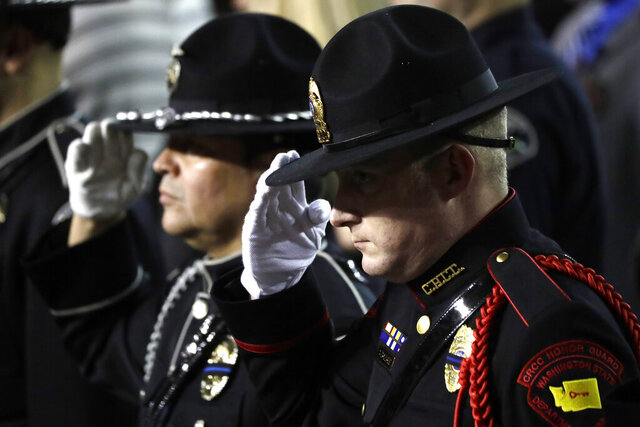 A Washington state Dept. of Corrections officer salutes Monday, Dec. 30, 2019 during the memorial service for Pierce County Sheriff's Deputy Cooper Dyson in Tacoma, Wash. Dyson died on December 21, 2019, after his patrol car crashed into a building while he was on his way to back up two fellow officers who were responding to an urgent domestic violence call. (AP Photo/Ted S. Warren)