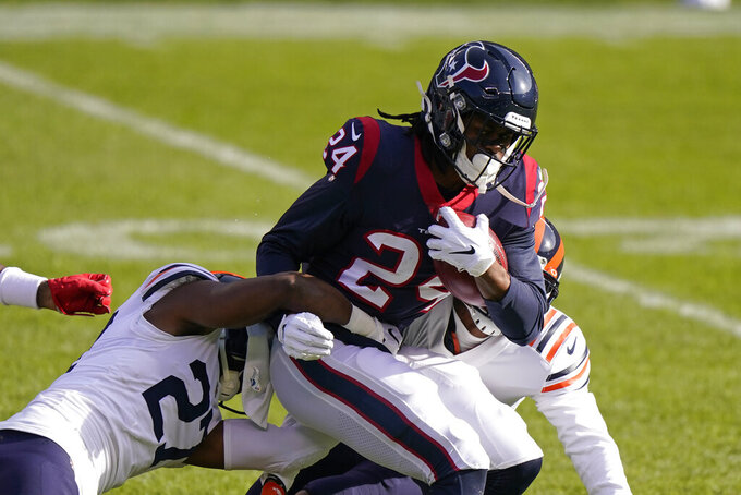 Houston Texans' C.J. Prosise (24) is tacked by Chicago Bears' Sherrick McManis (27) during the first half of an NFL football game, Sunday, Dec. 13, 2020, in Chicago. (AP Photo/Nam Y. Huh)