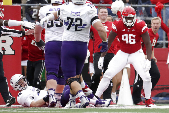 Rutgers defensive lineman Willington Previlon (96) celebrates after sacking Northwestern quarterback Clayton Thorson, left, for a safety during the first half of an NCAA college football game, Saturday, Oct. 20, 2018, in Piscataway, N.J. (AP Photo/Julio Cortez)