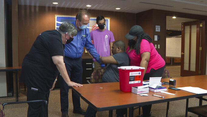 In this image made from video, a health care professional and representatives of JARC, a nonprofit dedicated to assisting those with developmental disabilities, try to persuade Noah Lebon to take a COVID-19 vaccine shot on Thursday, May 20, 2021, in Bloomfield Hills, Mich. Noah's mother, LaQuae Lebon, is standing beside her son in the vaccine clinic. (AP Photo/Mike Householder)