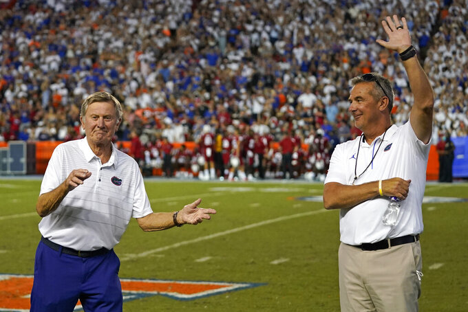 Former Florida head coaches Steve Spurrier, left, and Urban Meyer are recognized during a timeout in the first half of an NCAA college football game between Florida and Florida Atlantic, Saturday, Sept. 4, 2021, in Gainesville, Fla. Meyer is coach of the NFL's Jacksonville Jaguars. (AP Photo/John Raoux)