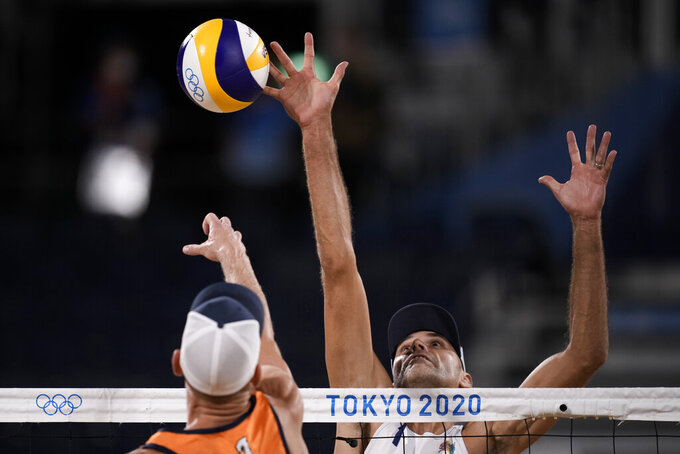 iPhilip Dalhausser, of the United States, blocks against Alexander Brouwer, of the Netherlands, during a men's beach volleyball match at the 2020 Summer Olympics, Saturday, July 24, 2021, in Tokyo, Japan. (AP Photo/Felipe Dana)