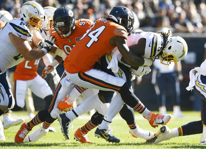 Los Angeles Chargers running back Melvin Gordon (25) is tackled by Chicago Bears outside linebacker Leonard Floyd (94) during the first half of an NFL football game, Sunday, Oct. 27, 2019, in Chicago. (AP Photo/Paul Beaty)