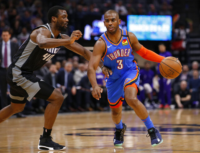 Oklahoma City Thunder guard Chris Paul, right, drive against Sacramento Kings forward Harrison Barnes, left, during the first quarter of an NBA basketball game in Sacramento, Calif., Wednesday, Jan. 29, 2020. (AP Photo/Rich Pedroncelli)