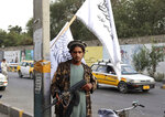 A Taliban fighter holds his weapon under Taliban flags hanging on a street in Kabul, Afghanistan, Monday, Aug. 30, 2021. Many Afghans are anxious about the Taliban rule and are figuring out ways to get out of Afghanistan. But it's the financial desperation that seems to hang heavy over the city. (AP Photo/Khwaja Tawfiq Sediqi)