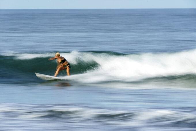 Surfer Anat Lelior, of Israel, rides a wave during a practice session at Tsurigasaki beach at the Tokyo 2020 Olympics in Ichinomiya, Japan, Wednesday, July 21, 2021. (AP Photo/David Goldman)