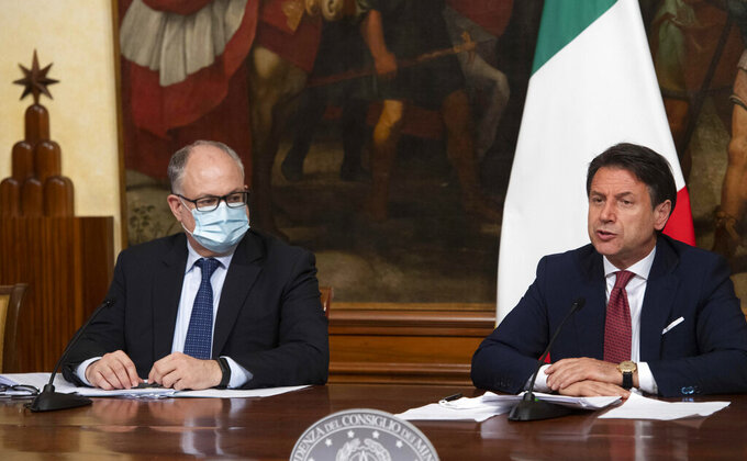 Italian Prime Minister, Giuseppe Conte, right, with Economy Minister Roberto Gualtieri, left, announces the latest set of measures under another emergency decree during the coronavirus pandemic, Friday, Aug. 7, 2020, in Rome, Italy. (Claudio Peri/Pool Photo via AP)