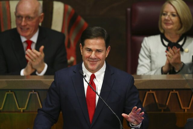 FILE - In this Jan. 13, 2020 file photo Arizona Republican Gov. Doug Ducey, foreground, gestures during his State of the State address as Senate president Karen Fann, R-Prescott, right, and House Speaker Rusty Bowers, R-Mesa, left, listen in on the opening day of the legislative session at the Capitol in Phoenix. Ducey and Republican lawmakers have pulled a contentious proposal to enshrine a ban on so-called