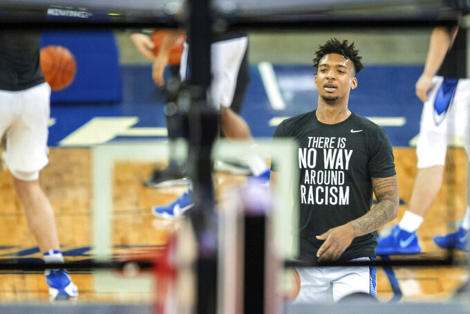"Creighton's Antwann Jones wears a ""There is no way around racism"" shirt while warming up for the team's NCAA college basketball game against Butler on Saturday, March 6, 2021, in Omaha, Neb. (Chris Machian/Omaha World-Herald via AP)"