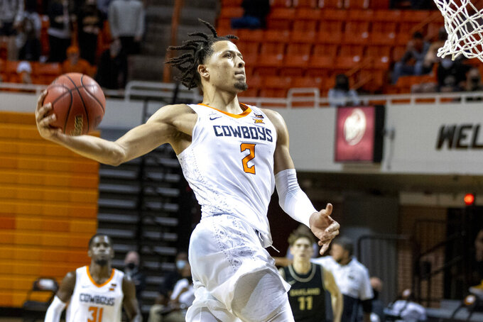 FILE - In this Dec. 5, 2020, file photo, Oklahoma State's Cade Cunningham slam-dunks the ball during the second half of the NCAA college basketball game against Oakland in Stillwater, Okla. Cunningham is The Associated Press Big 12 newcomer of the year and a member of the All-Big 12 first team, announced Tuesday, March 9, 2021. (AP Photo/Mitch Alcala, File)