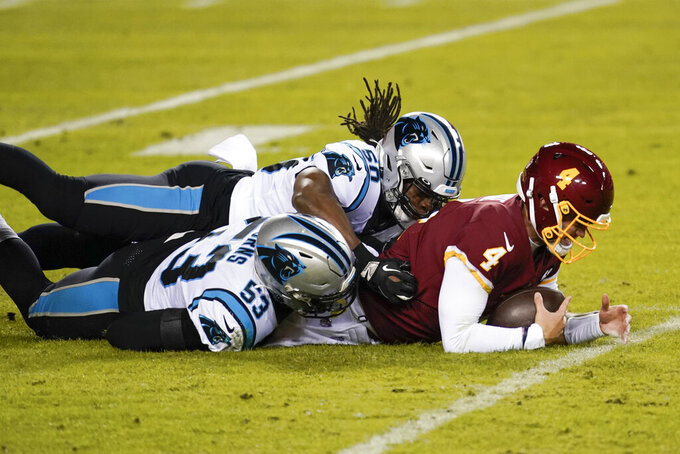 Washington Football Team quarterback Taylor Heinicke (4) is tackled by Carolina Panthers defensive end Brian Burns (53) and linebacker Julian Stanford (50) near the end of an NFL football game, Sunday, Dec. 27, 2020, in Landover, Md. Carolina won 20-13 (AP Photo/Mark Tenally)