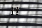 In this July 20, 2018, photo, people walk in a building in Tokyo. Japan reports its economy resumed its longtime expansion in the last quarter as consumers and businesses stepped up spending. (AP Photo/Eugene Hoshiko)