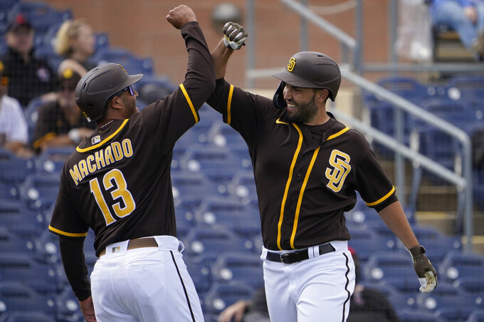 San Diego Padres Eric Hosmer, right, celebrates his home run with teammate Manny Machado (13) in the fourth inning of a spring training baseball game against the Cleveland Indians, Thursday, March 11, 2021, in Peoria, Ariz. (AP Photo/Sue Ogrocki)