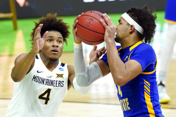 West Virginia's Miles McBride, left, and Morehead State's Johni Broome, right, battle for the ball during the first half of a college basketball game in the first round of the NCAA tournament at Lucas Oil Stadium Friday, March 19, 2021, in Indianapolis. (AP Photo/Mark Humphrey)
