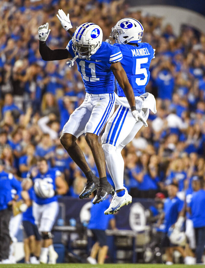 Brigham Young defensive back Isaiah Herron (11) and defensive back D'Angelo Mandell (5) celebrate a fumble recovery during the first half of an NCAA college football game against Utah Saturday, Sept. 11, 2021, in Provo, Utah. (AP Photo/Alex Goodlett)