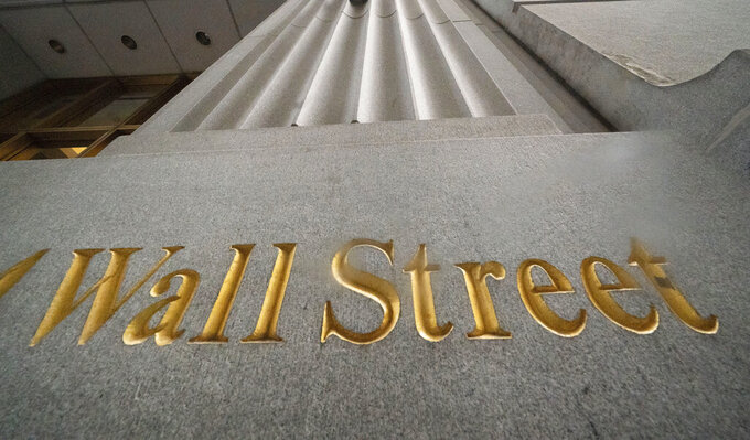 FILE - In this Nov. 5, 2020 file photo, a sign for Wall Street is carved in the side of a building, in New York.  Stocks are opening broadly higher on Wall Street, Friday, May 21, 2021, bringing the S&P 500 out of the red for the week. (AP Photo/Mark Lennihan, File)