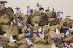 Muslim pilgrims pray on top of the rocky hill known as the Mountain of Mercy, on the Plain of Arafat, beside inscriptions which were left by pilgrims from previous years, during the annual hajj pilgrimage, near the holy city of Mecca, Saudi Arabia, Monday, July 19, 2021. The coronavirus has taken its toll on the hajj for a second year running. What once drew some 2.5 million Muslims from all walks of life from across the globe, the hajj pilgrimage is now almost unrecognizable in scale. (AP Photo/Amr Nabil)