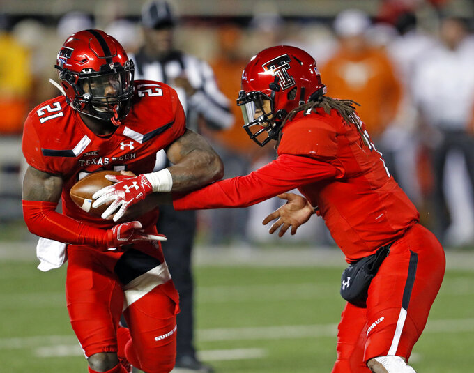 Texas Tech's Jett Duffey (7) hands the ball off to Da'Leon Ward (21) during the first half of an NCAA college football game against Texas, Saturday, Nov. 10, 2018, in Lubbock, Texas. (AP Photo/Brad Tollefson)
