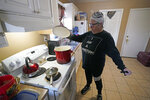 Nancy Wilson boils water in her home Friday, Feb. 19, 2021, in Houston. She does not have full running water as the city remains under a boil water notice and many residents lack water at home due to frozen or broken pipes. (AP Photo/David J. Phillip)