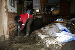 Yoshiki Yoshimura, 17, cleans up mud at his home after Typhoon Hagibis passed through the neighborhood, Tuesday, Oct. 15, 2019, in Nagano, Japan. More victims and more damage have been found in typhoon-hit areas of central and northern Japan, where rescue crews are searching for people still missing. (AP Photo/Jae C. Hong)