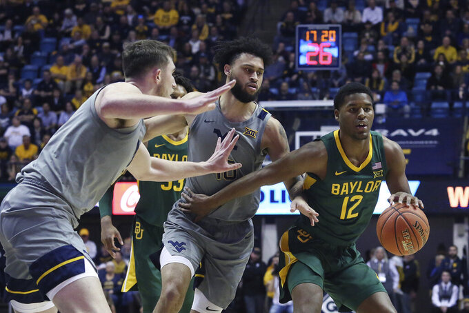 Baylor guard Jared Butler (12) goes up court against West Virginia forward Logan Routt, left, and guard Jermaine Haley (10) during the first half of an NCAA college basketball game Saturday, March 7, 2020, in Morgantown, W.Va. (AP Photo/Kathleen Batten)