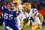 LSU quarterback Max Johnson (14) scrambles past Florida defensive lineman Kyree Campbell (55) during the first half of an NCAA college football game Saturday, Dec. 12, 2020, in Gainesville, Fla. (AP Photo/John Raoux)