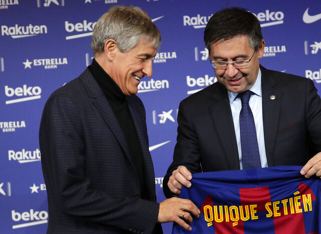 Soccer coach Quique Setien smiles with FC Barcelona's President Josep Maria Bartomeu, right, while being officially introduced as the club's new coach at the Camp Nou stadium in Barcelona, Spain, Tuesday, Jan. 14, 2020. Barcelona made a rare coaching change midway through the season, replacing Ernesto Valverde with former Real Betis manager Quique Setien on Monday. (AP Photo/Emilio Morenatti)